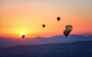 hot air balloons in front of sunset