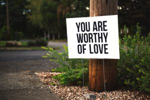 "sign attached to pole saying ""you are worthy of love"""