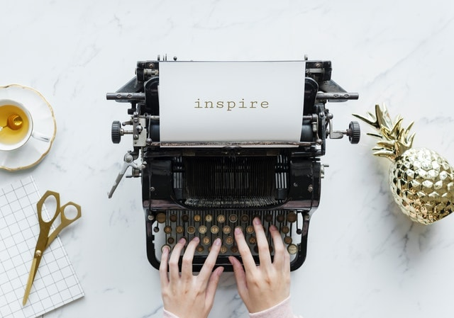 an old fashioned type writer with the words inspire on the paper sitting in the type written