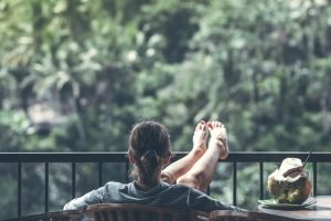 woman sitting on a balcony overlooking forest with feet up on rail