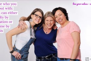 three women smiling with arms around each other