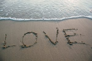 love written in the sand on a beach by the tideline