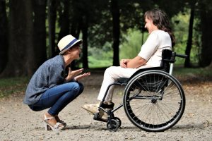 woman talking to a woman in a wheelchair