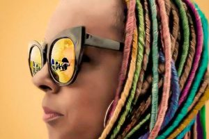 woman with multi-coloured dreadlocks wearing sunglasses