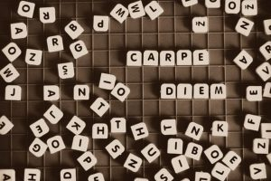 individual letter tiles scattered on a table with two words spelt out - carpe diem